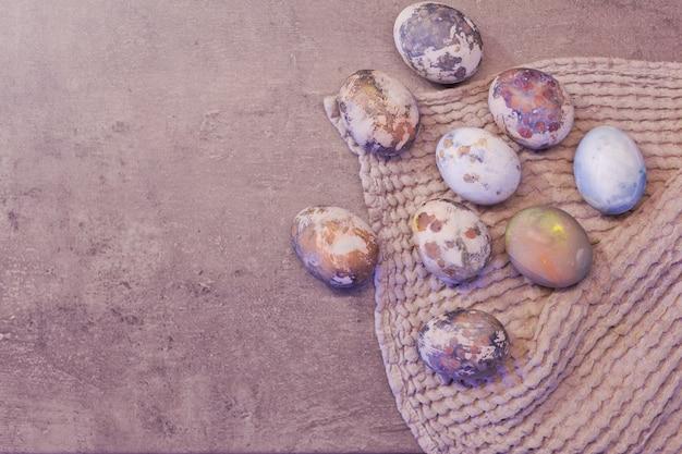 Joyeuses pâques. série d'oeufs avec effet pierre marbrée peints sur fond de béton gris naturel avec espace vide pour le texte. vue de dessus, mise à plat