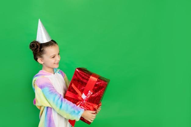 Joyeuses petites filles dans un costume de licorne sur fond vert