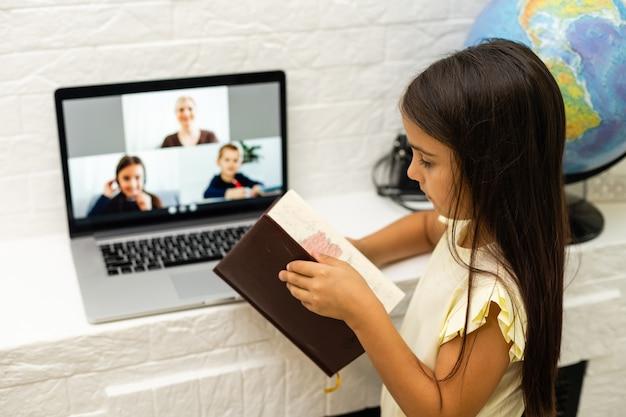 Joyeuses petites filles utilisant un ordinateur portable, étudiant via un système d'apprentissage en ligne