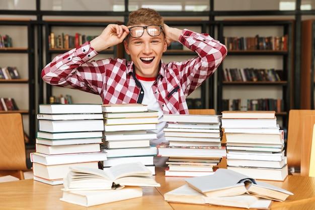 Joyeux adolescent assis à la bibliothèque