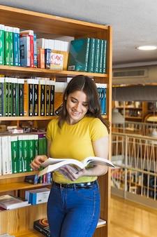 Joyeux adolescent lire livre dans la bibliothèque de l'école