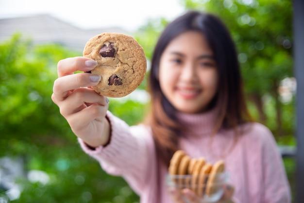 Joyeux adolescent mignon tenant un biscuit à la maison