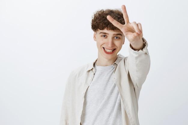 Joyeux adolescent posant contre le mur blanc