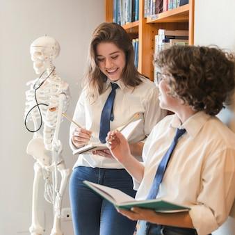 Joyeux adolescents étudient dans la bibliothèque