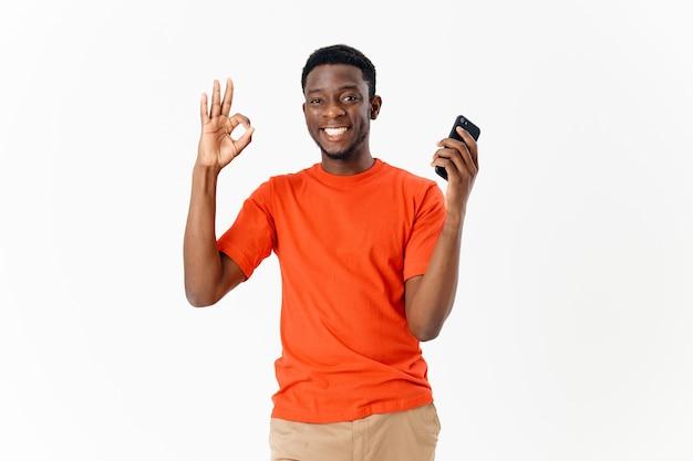 Joyeux afro-américain avec téléphone dans les mains geste respectueux avec lumière de communication à la main