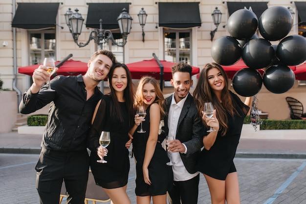 Joyeux amis buvant du champagne à la fête en plein air