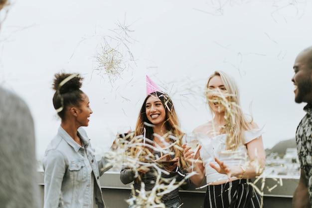 Joyeux amis célébrant une fête d'anniversaire sur un toit