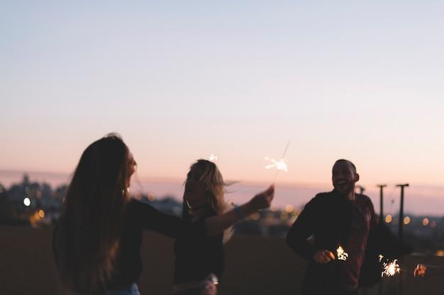 Joyeux amis avec des cierges magiques dans la nuit