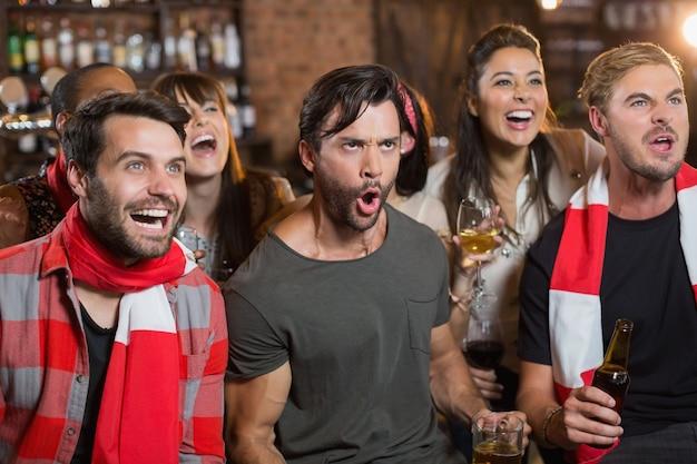Joyeux amis criant dans un pub