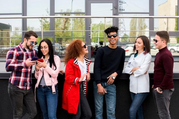 Joyeux amis debout devant le bâtiment de verre