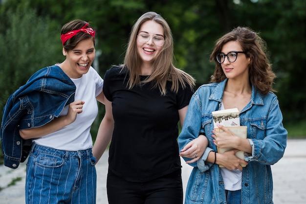 Joyeux amis debout sur le trottoir du parc