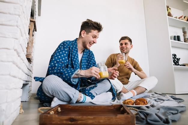 Joyeux amis masculins dégustant un délicieux petit déjeuner assis sur le sol à la maison