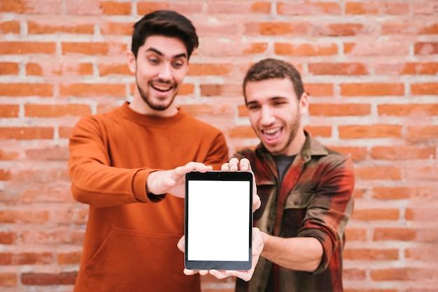 Joyeux amis montrant une tablette à la caméra
