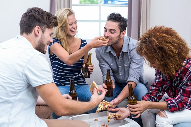 Joyeux amis multiethniques appréciant bière et pizza