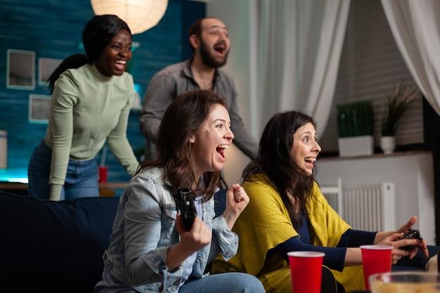 Joyeux amis multiethniques célébrant la victoire tout en jouant à des jeux vidéo en ligne assis sur un canapé à l'aide d'un contrôleur sans fil la nuit dans le salon de la maison, assis sur un canapé.
