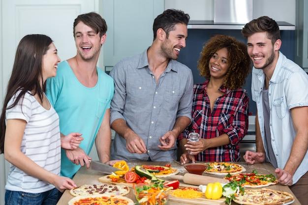 Joyeux amis multiethniques préparant une pizza à la maison