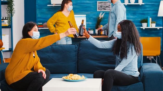 Joyeux amis multiraciaux avec des masques de protection buvant de la bière, parlant s'amusant ensemble profitant d'une conversation agréable d'amitié multiethnique