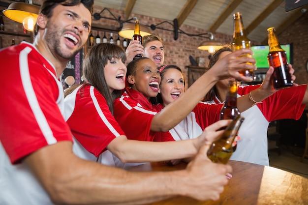 Joyeux amis à la recherche de suite tout en tenant des bouteilles de bière