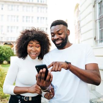 Joyeux amis regardant mobile