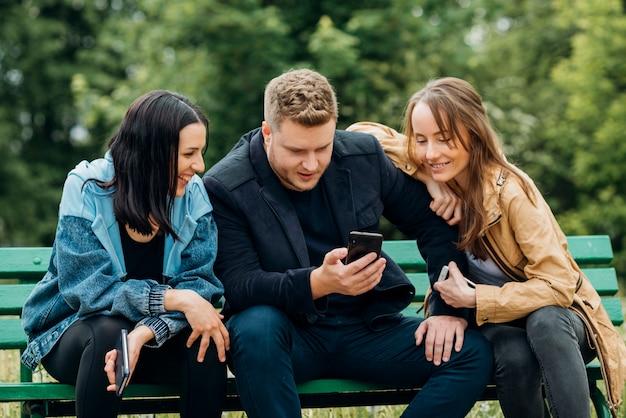 Joyeux amis se détendre sur un banc dans le parc