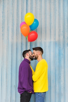 Joyeux amoureux gays s'embrasser et tenant des ballons