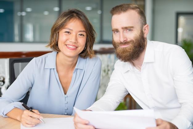 De joyeux analystes travaillant sur des rapports de marketing