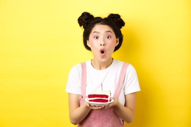 Joyeux anniversaire asiatique fille avec un maquillage lumineux, soufflant une bougie sur un gâteau, faisant un souhait, debout sur le jaune.