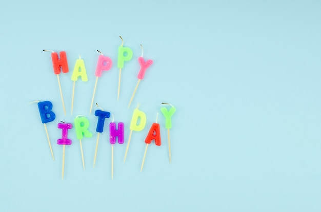 Joyeux anniversaire bougies colorées sur fond bleu