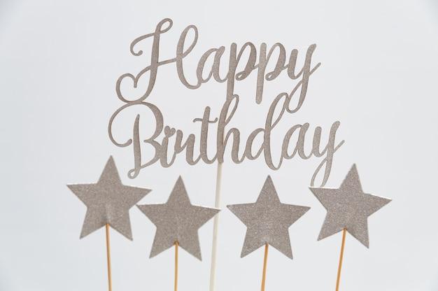 Joyeux anniversaire écrit en lettres argentées avec des formes d'étoiles.