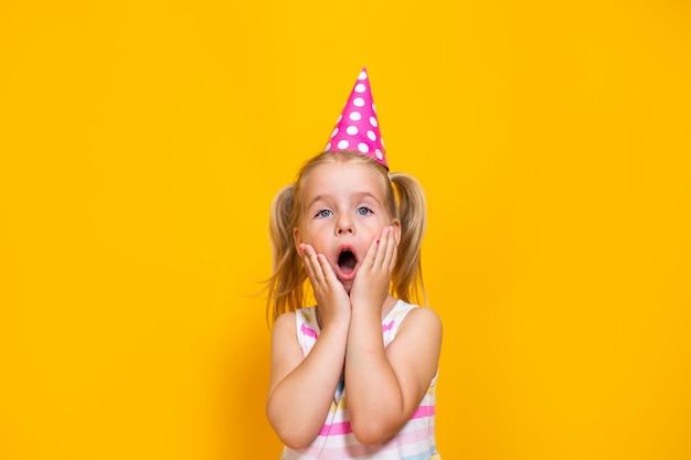 Joyeux anniversaire enfant fille en bonnet rose sur mur jaune coloré. tout-petit tenant sa bouche avec les mains.