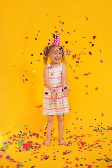 Joyeux anniversaire enfant fille souriante dans une tasse rose entouré de confettis volants sur un mur jaune coloré. célébration, enfance, émotions.