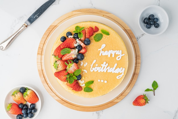 Joyeux anniversaire gâteau au fromage aux fruits frais avec joyeux anniversaire sur le concept de gâteau avec gâteau aux fruits aux fraises kiwi. concept alimentaire.