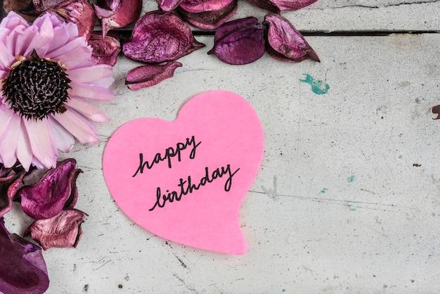 Joyeux anniversaire en papier en forme de coeur avec des fleurs roses