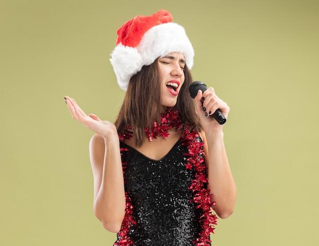 Joyeux aux yeux fermés jeune belle fille portant un chapeau de noël avec guirlande sur le cou tenant le microphone et chante isolé sur fond vert olive