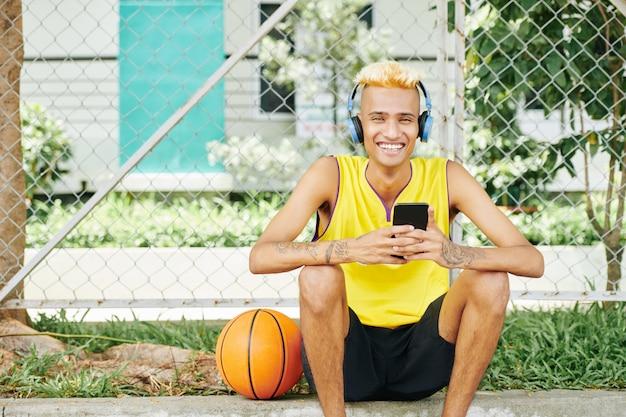 Joyeux basketteur se reposant à l'extérieur