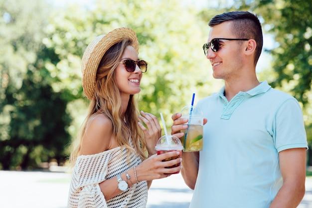 Joyeux beau couple s'amuser ensemble, boire des boissons fraîches à l'extérieur