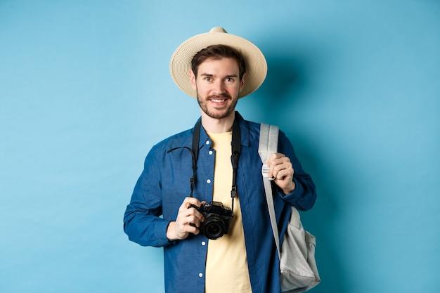 Joyeux beau mec partant en vacances, portant un chapeau d'été et tenant un sac à dos avec appareil photo pour des photos, souriant excité de vacances, debout sur fond bleu.