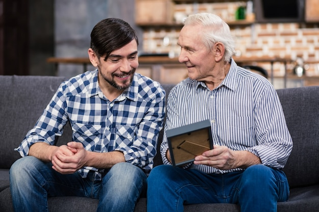 Joyeux beau père âgé et son fils se reposant à la maison tout en tenant un cadre photo