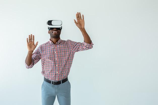 Joyeux bel homme afro-américain testant des lunettes vr en se tenant debout contre un mur blanc