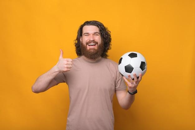 Joyeux bel homme aux cheveux longs tenant un ballon de football et montrant le geste du pouce vers le haut