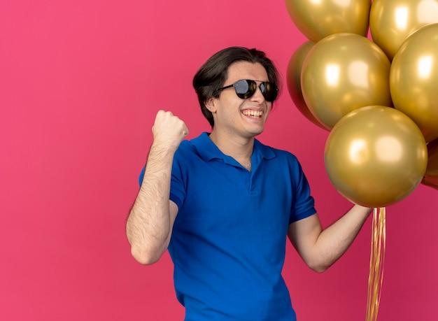 Joyeux bel homme caucasien à lunettes de soleil tient des ballons à l'hélium et garde le poing levé