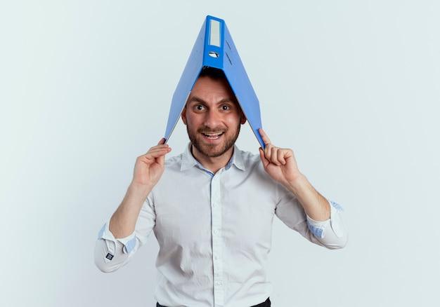 Joyeux bel homme détient le dossier de fichiers sur la tête isolé sur un mur blanc