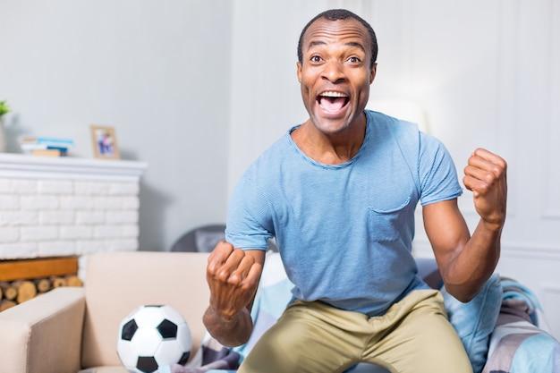 Joyeux bel homme heureux souriant et se sentant submergé par les émotions tout en soutenant son équipe de football