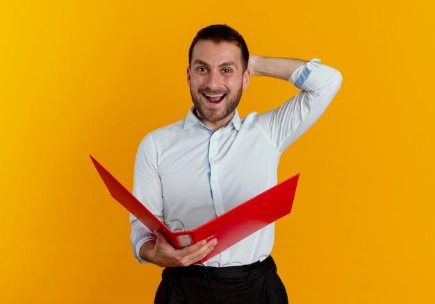 Joyeux bel homme met la main derrière la tête tenant le dossier de fichiers isolé sur mur orange