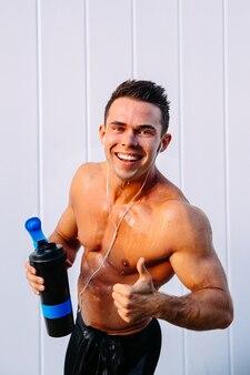 Joyeux bel homme musclé avec biceps dans les écouteurs montrant un pouce vers le haut