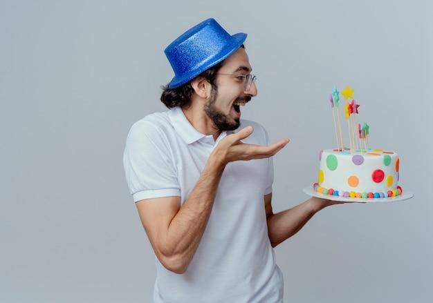 Joyeux bel homme portant des lunettes et un chapeau bleu tenant et points avec la main au gâteau isolé sur fond blanc