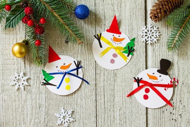 Joyeux cadeau de bonhomme de neige de noël sur la table en bois artisanat fait main pour des enfants