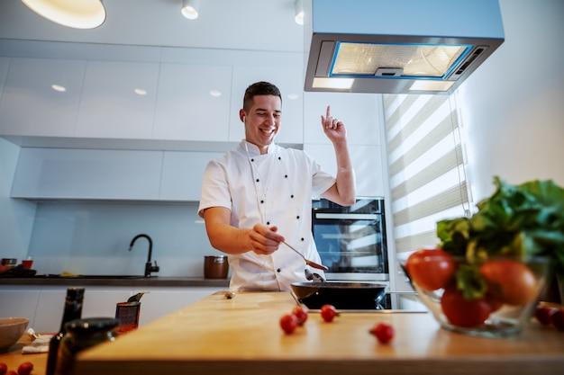 Joyeux chef caucasien en uniforme appréciant la musique et préparant la sauce tomate en se tenant debout dans la cuisine.