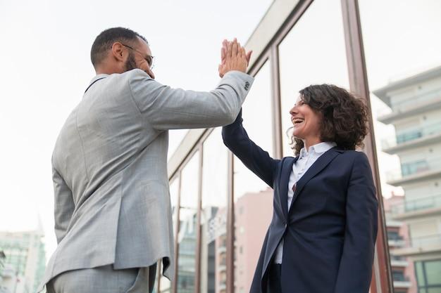 Joyeux collègues d'affaires donnant cinq haut