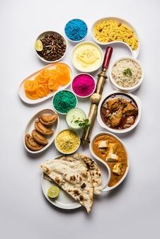 Joyeux concept sacré montrant un assortiment de plats indiens pour le déjeuner comme du poulet paneer beurre masala naan jeera riz noir chana fry jalebi ras malai thandai et farsan avec des couleurs holi et pichkari